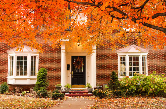Red brick house entrance with seasonal wreath on door and porch and bay windows on autumn day with leaves on the ground and hydrageas still in bloom - colorful foliage