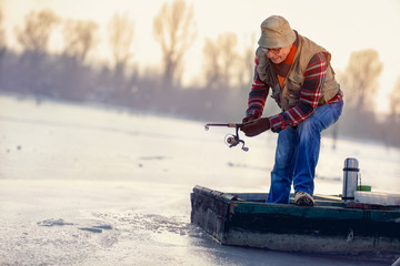 Winter season - fisherman fishing on the frozen lake