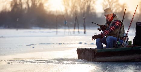 Happy man on winter fishing on the frozen lake