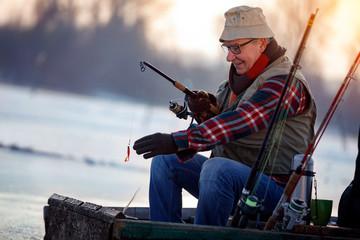 Winter hobby -elderly man fishing