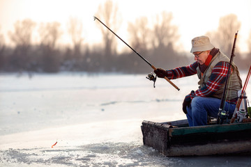 elderly man fishing in the winter on the lake