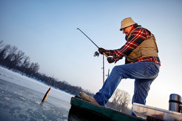 Fisherman catch fish on the frozen river in winter