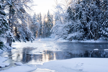 Sunrise river in a cold winter landscape with snow and frost