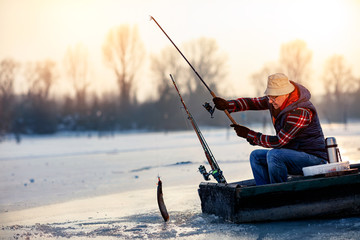 Happy fisherman catch fish on the frozen river in winter