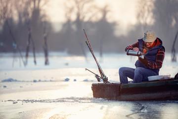 Winter season- senior man sitting on frozen lake and drink tea