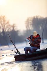 Fisherman sitting on frozen lake and drink tea