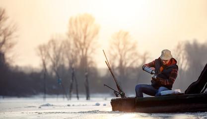 Fishing on ice- senior man sitting on frozen lake and drink tea