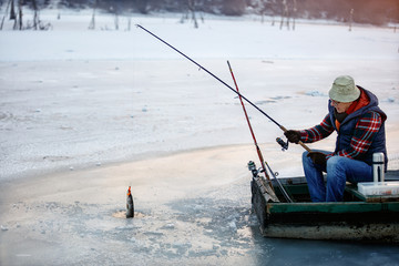 Ice fishing on frozen lake- fisherman fishing on ice
