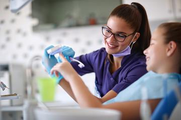 Dentist educates little girl how to brush teeth