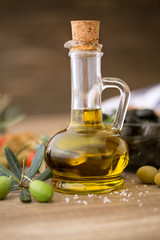 Olive oil and olive branch on the wooden table.