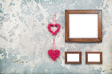 Photo or picture frames blanks and pair of handmade Valentine's day love hearts hanging on vintage aged grunge textured concrete wall background. Retro old style filtered photo
