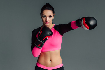 Close up portrait of a young sportswoman in boxing gloves. Pretty female brunete boxer. Healthy lifestyle concept. Girl fighter.