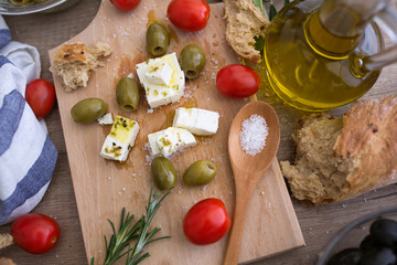 top view Greek cheese feta with virgin olive oil, green olives and fresh vegetables.