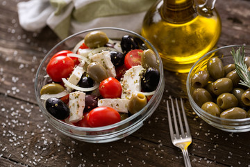 Greek salad with fresh vegetables, feta cheese and green olives wooden table .