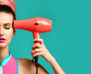 Happy young brunette woman with red hair dryer on blue mint background