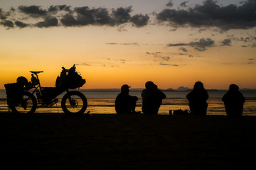 Four people sit on a cliff above the sea in Baja California at sunset next to a loaded touring bicycle with a view of the ocean