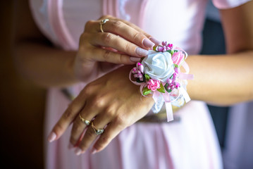 Dressing a boutonniere on the hand of a bridesmaid