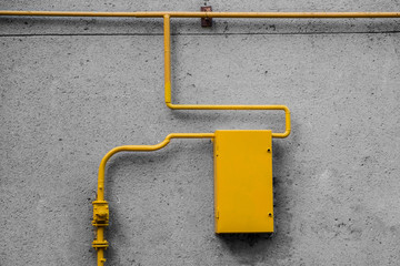 a yellow gas pipe and a distribution board on a gray wall