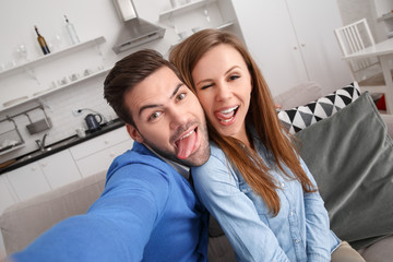 Young couple together at home weekend taking selfie tongue out