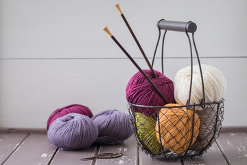Colorful spring wool yarn in an iron basket with wooden knitting needles