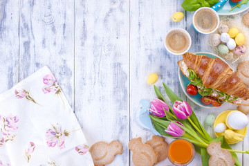 Easter breakfast flat lay with, bread toast with fried egg and gre, colored quail eggs and spring holidays decorations. Top view. Copy space. croissants for breakfast. Free space for text or postcard.