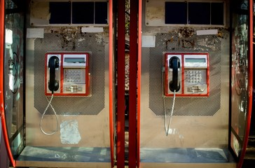 two retro red phones booth boxes close up, isolated  on sunny day technology of 20th century