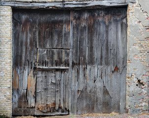 Old, dirty and weathered closed wooden barn door