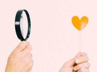 Person looking at heart through magnifying glass