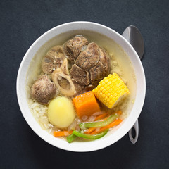 Traditional Chilean Cazuela de Vacuno or Cazuela de Carne, a beef soup with potato, corn, pumpkin, carrot, bell pepper, onion and rice, photographed overhead on slate with natural light