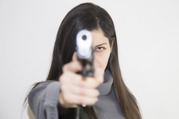 Beautiful young girl with a gun, isolated on white background. A teenage girl with holds a gun in her hands.