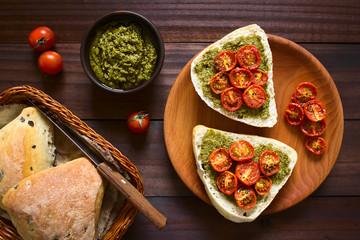 Olivenbrötchen mit Pesto und gerösteten Kirschtomaten auf Holzteller, fotografiert mit natürlichem Licht