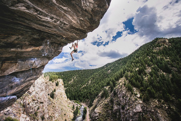 female climber with feet in the air on an overhanging roof