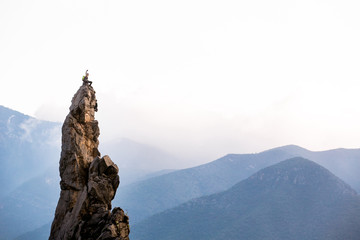female climber taking a selfie on top of a rock tower