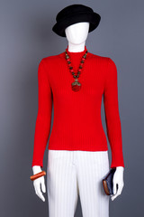 Mannequin in black hat and red sweater. Red pullover, white trousers, jewelry and wallet. Ladies fashion look.