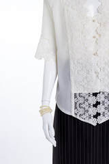Close up mannequin in elegant female clothing. White silk blouse and black skirt, copy space. Pearl beads on mannequin hand. Ladies clothes and accessories.