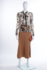 Chiffon patterned blouse and brown skirt. Female mannequin in skirt and blouse on white background. Ladies elegance and style.