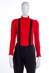 Black cotton trousers with suspenders. Red warm pullover for women. Female trendy look.