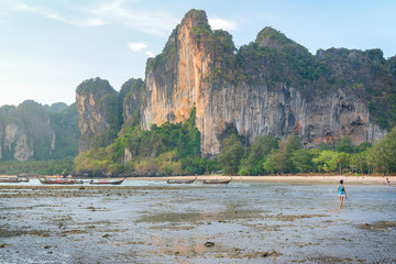 Woman walking on Railay beach at sunset, Krabi, Thailand