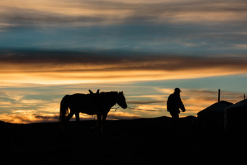 Silhouette of a Mongolian nomad leading his horse back to the family ger tent