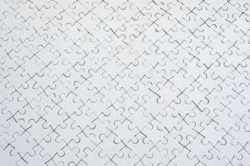 Close up texture of a white jigsaw puzzle in assembled condition. Top view. Many components of a large whole mosaic are united