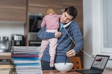 Multitasking father is babysitting and working at home.