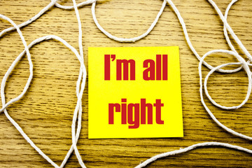 I am all right- word on yellow sticky note in wooden background. Bussines concept.