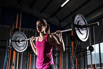Athletic girl works out at the gym with a barbell