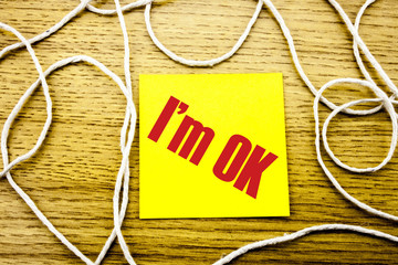 I am OK- word on yellow sticky note in wooden background. Bussines concept.