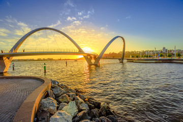 Poster Oceania Scenic and iconic Elizabeth Quay Bridge at sunset light on Swan River at entrance of Elizabeth Quay marina. The arched pedestrian bridge is a new tourist attraction in Perth, Western Australia.