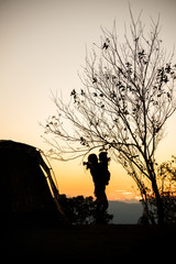 Silhouette of mother with her daughter near the tent and tree at sunset