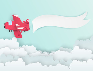 Airplane aerial view paper art with paper banner for text. Flying origami red plane. Blue sky background with fluffy clouds. Trendy paper art style