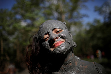 "A member of the ""Bloco Pretinhos do Mangue"" (Block of Blackheads from Mud) group performs during carnival festivities in Curuca"