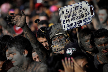 "A member of the ""Bloco Pretinhos do Mangue"" (Block of Blackheads from Mud) group holds a sign during carnival festivities in Curuca"