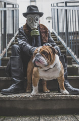 Mand with gas mask holding English bulldog,selective focus